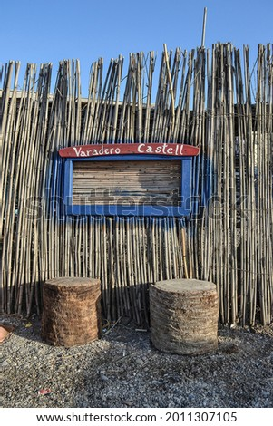 fence of sticks and ropes in Castell de Ferro with a sign that says Varadero Castell with two seats Foto stock ©