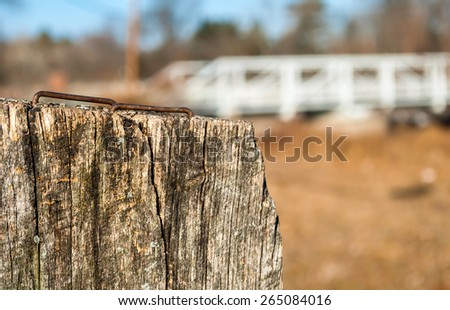 Fence post in remote area with iron bridge background, Wooden stump with rusty nails on top, fall weather, bark, artistic and abstract view. Depth of field on steel bridge