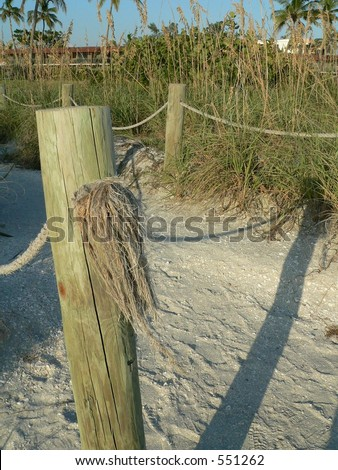 Fence post on beach path to motel in distance