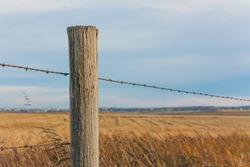 Fence Post with prairie landscape bokeh.