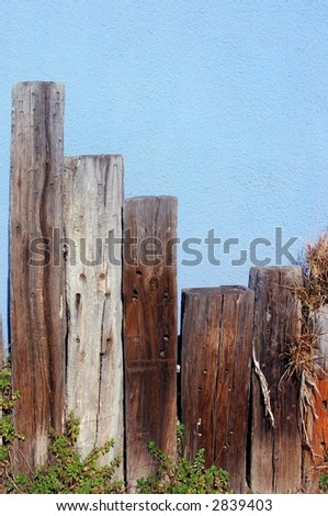 fence posts and blue wall