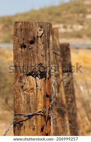 Fence posts in desert with barbed wire