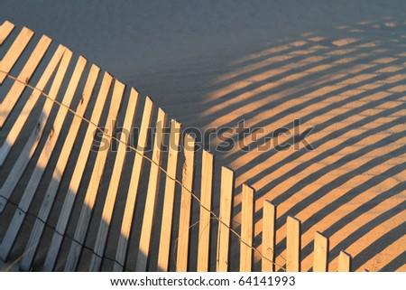 fence shadows and sand ripples on beach