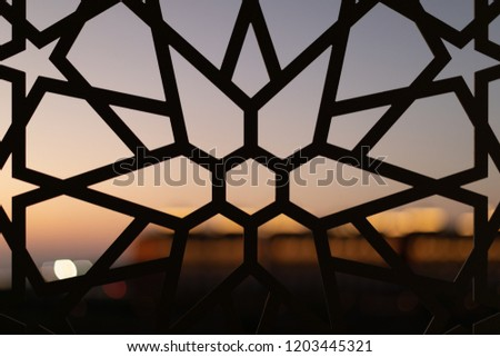 Fence with a floral pattern and stars at sunset. Oriental patterns. Turkish patterns and backgrounds #1203445321