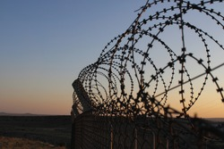 Fence with barbed wire and mesh at sunset. Private territory. Barbwire on sunset background. Prison concept. Barbed wire mesh fence against blue and orange sky. Border. Selective focus. Close up