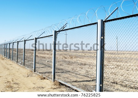 Fence with barbed wire on a background of blue sky