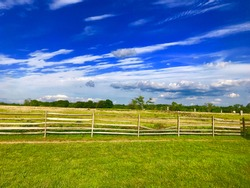 Fence with green grass and blue sky.  At Gettysburg Pennsylvania.