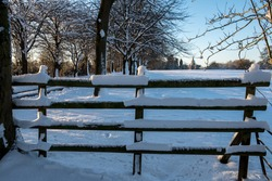 Fence with 4 wooden bars, covered in snow overlooking a field of snow and a church in the distance
