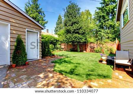 Fenced Backyard with house and garage and two doors
