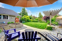 Fenced backyard with lawn, garden bed, shed with woods and pergola. View from patio area with chairs and umbrella