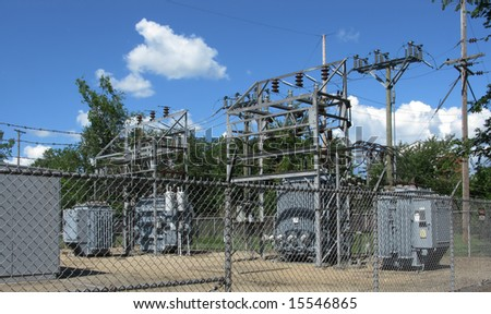 fenced electrical power substation with clouds background