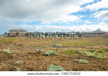 Fenced vacant land near some Australian new residential suburban houses. Concept of real estate development, housing, land for sale and a new suburb, Tarneit, Melbourne, VIC Australia. Imagine de stoc ©