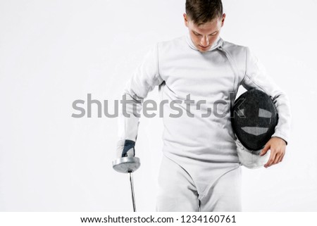 Fencer athlete wearing mask and white fencing costume and holding the sword, . Isolated on white background