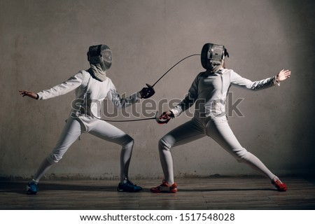 Photo of  Fencer woman with fencing sword. Fencers duel concept.