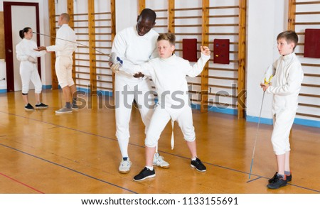 Fencing instructor explaining to young fencers effective movements and techniques at the training room
