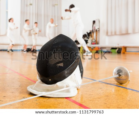 Fencing mask and foil lying on floor on background with group engaged in fencing indoors