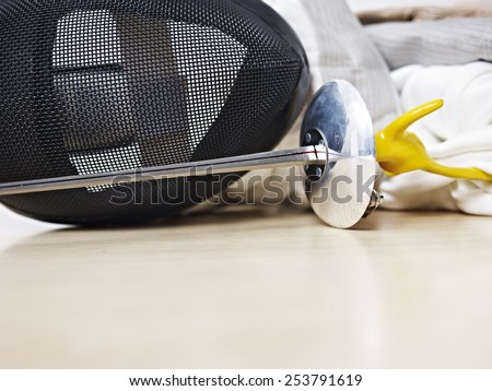 fencing mask and rapier on floor.