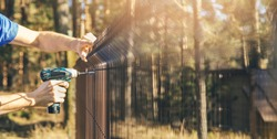 fencing - worker installing metal wire mesh fence panel