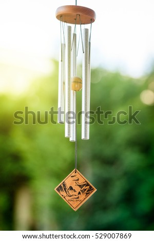 Feng shui chimes with nature in the background with a clear blue sky and defocused tree in the background on a sunny day #529007869