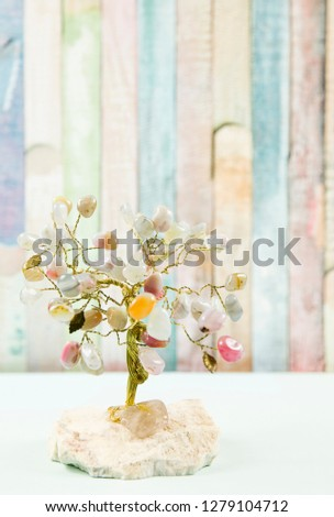 Feng shui gem tree, also called feng shui crystal tree is used for spiritual feng shui cures for love to feng shui for money. Isolated on colorful pastel wooden board background. #1279104712