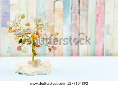 Feng shui gem tree, also called feng shui crystal tree is used for spiritual feng shui cures for love to feng shui for money. Isolated on colorful pastel wooden board background. #1279104892