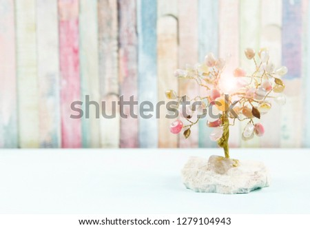 Feng shui gem tree, also called feng shui crystal tree is used for spiritual feng shui cures for love to feng shui for money. Isolated on colorful pastel wooden board background. Lens flare. #1279104943