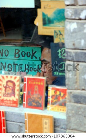 FENGHUANG - MARCH 23: A man inside a bookstore on March 23, 2012 in Fenghuang, China. China is the largest publisher of books in the world. Some 128,800 new titles of books were published in 2005.