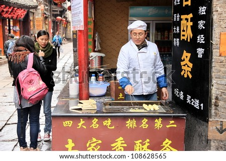 FENGHUANG - MARCH 23: Traditional street food on March 23, 2012 in Fenghuang County. According to the Food and Agriculture Organization, 2.5 billion people eat street food every day. - stock photo