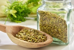 Fennel seeds in wooden spoon with glass vase close