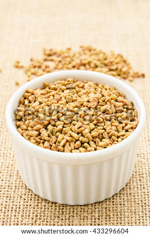 Fenugreek seeds in white bowl on sack background. #433296604
