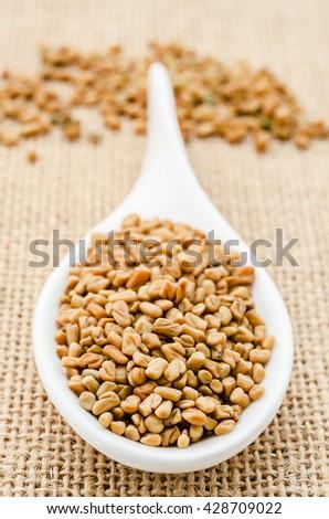 Fenugreek seeds in white spoon on sack background. #428709022