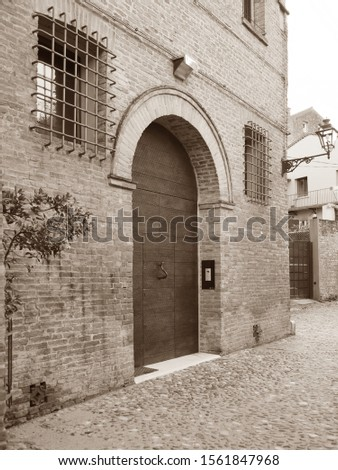 Ferrara, Italy. Ancient street, facade with large door. Sepia photo.