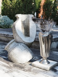 Ferrara, Italy. Certosa Monumental Cemetery. Old broken stone vase, next to it is a modern metal vase.