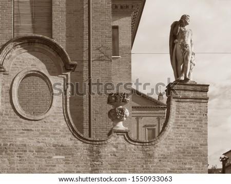Ferrara, Italy. Old town, corso Ercole I d'Este. Elegant perimeter wall with statue. Sepia photo.