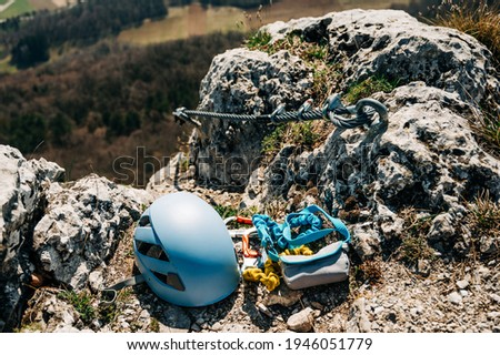 Ferrata climbing equipment. Via Ferrata set with two lanyards with carabiners, helmet with the steel cable in the background. Gear on the cliff at the top of the mountain. Foto d'archivio ©