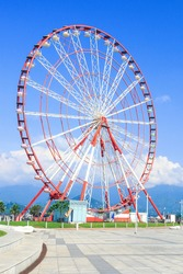 Ferris Wheel against the blue sky with clouds in the Resort Town, Sunny Day. Rotating Ferris wheel with cabins or capsules and center part. Concept of lifestyle, fun, growth, relax. Vertical photo.