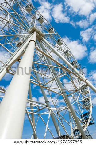 Ferris wheel an amusement-park or fairground ride consisting of a giant vertical revolving wheel with passenger cars suspended on its outer edge. #1276557895