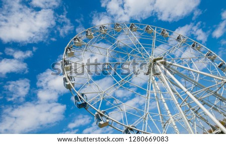 Ferris wheel an amusement-park or fairground ride consisting of a giant vertical revolving wheel with passenger cars suspended on its outer edge. #1280669083