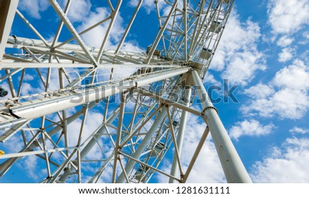 Ferris wheel an amusement-park or fairground ride consisting of a giant vertical revolving wheel with passenger cars suspended on its outer edge. #1281631111