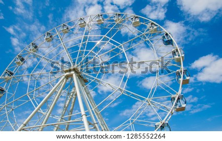 Ferris wheel an amusement-park or fairground ride consisting of a giant vertical revolving wheel with passenger cars suspended on its outer edge. #1285552264