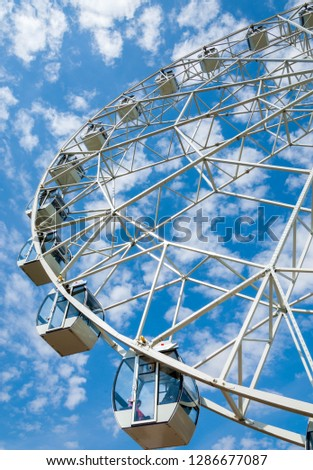 Ferris wheel an amusement-park or fairground ride consisting of a giant vertical revolving wheel with passenger cars suspended on its outer edge. #1286677087
