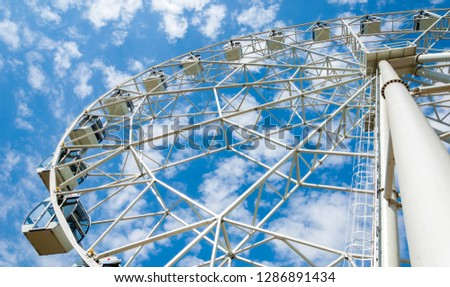 Ferris wheel an amusement-park or fairground ride consisting of a giant vertical revolving wheel with passenger cars suspended on its outer edge. #1286891434