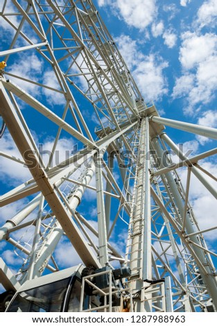 Ferris wheel an amusement-park or fairground ride consisting of a giant vertical revolving wheel with passenger cars suspended on its outer edge. #1287988963