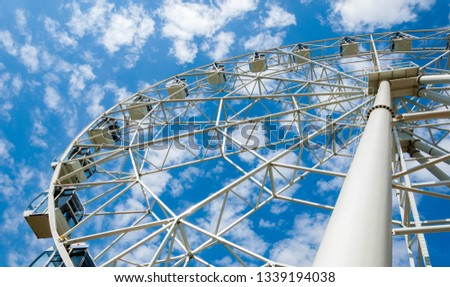 Ferris wheel an amusement-park or fairground ride consisting of a giant vertical revolving wheel with passenger cars suspended on its outer edge. #1339194038