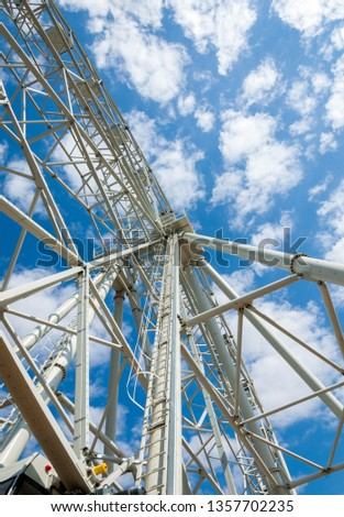 Ferris wheel an amusement-park or fairground ride consisting of a giant vertical revolving wheel with passenger cars suspended on its outer edge. #1357702235