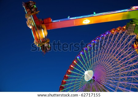 Ferris wheel and carnival ride at night. Motion blur