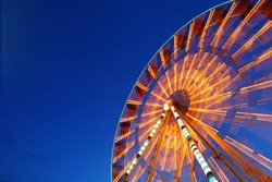 Ferris wheel and rollercoaster in motion at amusement park at night