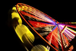 Ferris Wheel at night with many colorful lights an long time exposure that leaves light traces and paintings on a funfair in Germany is a huge attraction for joyriders