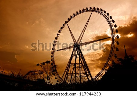 Ferris Wheel at sunset. Some Chinese words in the photo mean roller coaster and not an ad.