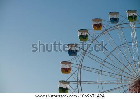 Ferris wheel blue sky close up side on ammusement ride background